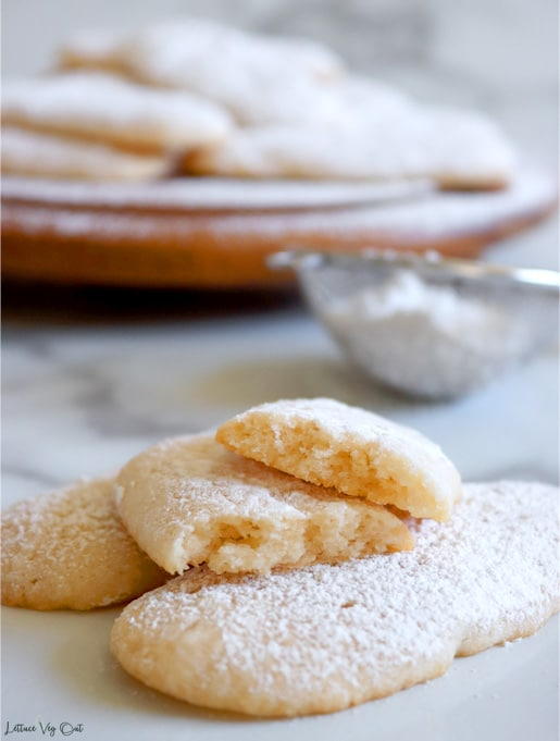 Two lady finger cookies with a third cut in half and stacked on to, sitting on white-grey marble. Blurred wood board with icing-sugar coated ladyfingers sits in the back with a metal sifter full of icing sugar.