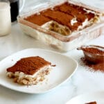 White plate with square of vegan tiramisu (layers of vanilla ladyfingers, cream and cocoa powder on top). A second plate with tiramisu slice in bottom right corner with a small metal sifter of cocoa powder to the center right of image. Square glass dish of sliced tiramisu in back with coffee and milk in glass mugs.