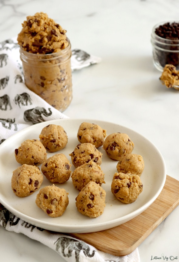 Plate covered with chocolate chip cookie dough balls on light wood board with small jar of raw dough to the back left. Small jar of chocolate chips and spoonful of raw dough to the back right corner. White-grey patterned towel along the left edge and white-grey marble background.