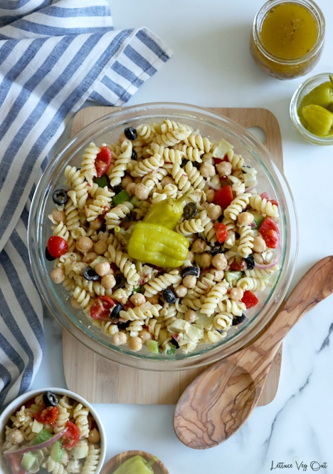 Top view of large glass bowl filled with tossed pasta salad and garnished with two pickled peppers. Bowl on wood board with wood spoon on it. White-grey marble background with white-blue striped towel along left edge of image. Salad dressing and pickled peppers in top right corner; bowl of pasta salad in bottom left corner.
