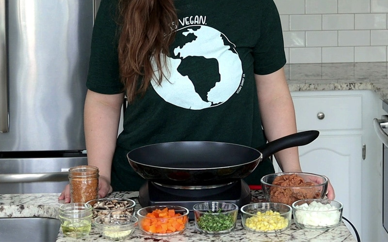 Nicole stands behind the counter which is covered with a large black pan sitting on an electric cooking element and surrounded by small glass dishes filled with quesadilla ingredients (taco seasoning, oil, mushrooms, garlic, orange pepper, cilantro, corn, white onion, refried beans). She wears a dark green shirt with a white earth image on it and her head is cropped out.