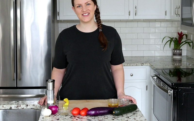 Nicole stands behind a counter with a large wood cutting board in front of her and ingredients for vegan tian (zucchini, eggplant, tomatoes, red onion, garlic, salt, pepper and small jars hidden behind the vegetables). Nicole is smiling, wearing a black t-shirt with her long brown hair in a side briad.
