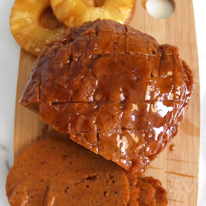 Meatless ham roast with pineapple rings sitting on wooden cutting board