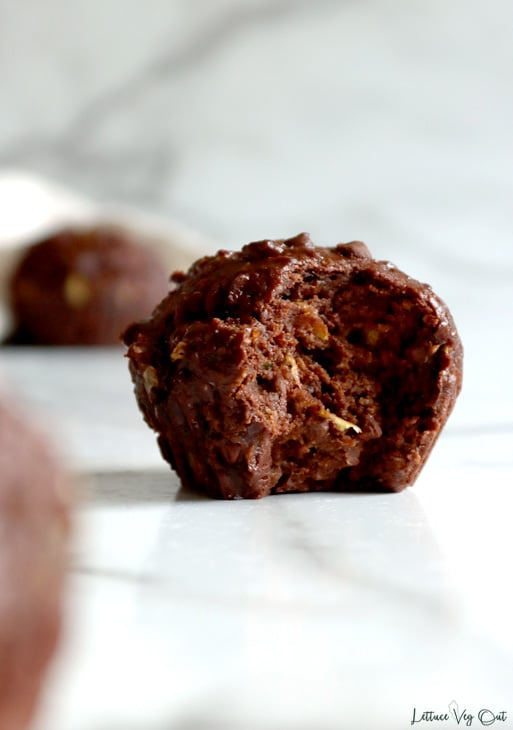 Double chocolate zucchini muffin with large bite taken, sitting on white-grey marble. A bit of a second muffin blurred in the foreground to the left with another whole muffin blurred in the background to the left, with a towel placed behind this muffin.