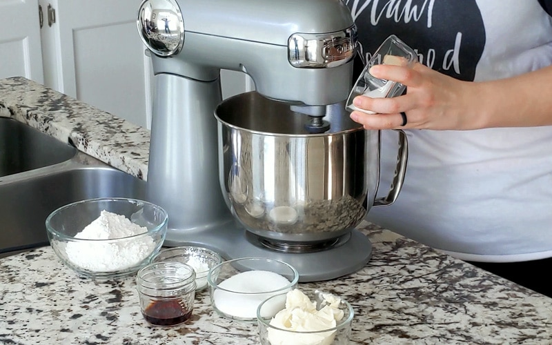 Grey stand mixer on granite counter top. A hand is holding a small glass bowl of sugar that is being tipped into the mixing bowl.