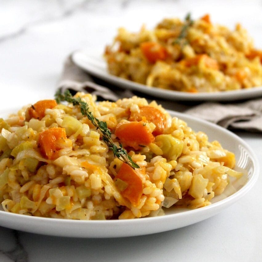 Two plates of vegan pumpkin leek risotto with creamy chunks of pumpkin showing through the arborio rice