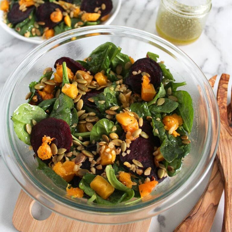 Two bowls of vegan salad with roasted pumpkin and beetroot with mixed greens