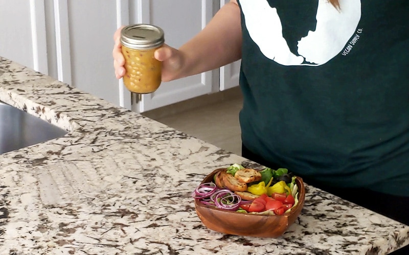 Hand holding small mason jar filled with dark yellow liquid with a few purple flecks. The jar is blurred as if in motion (being shaken). A small wood bowl filled with salad (red onion slices, tomato, croutons and lettuce) sits on the counter below the jar.