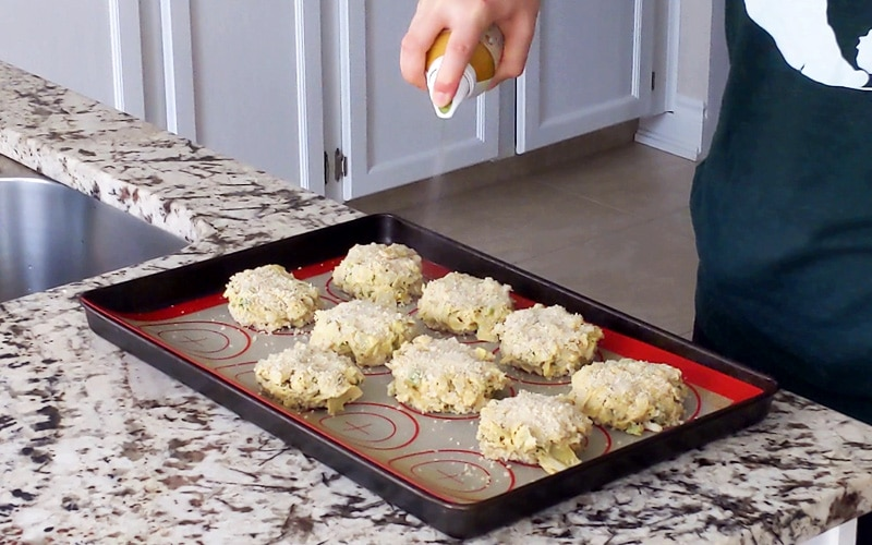 A hand holds an oil spray canister and is spraying oil onto breadcrumb-coated artichoke cakes that are arranged on a baking tray covered in a silicone baking mat.