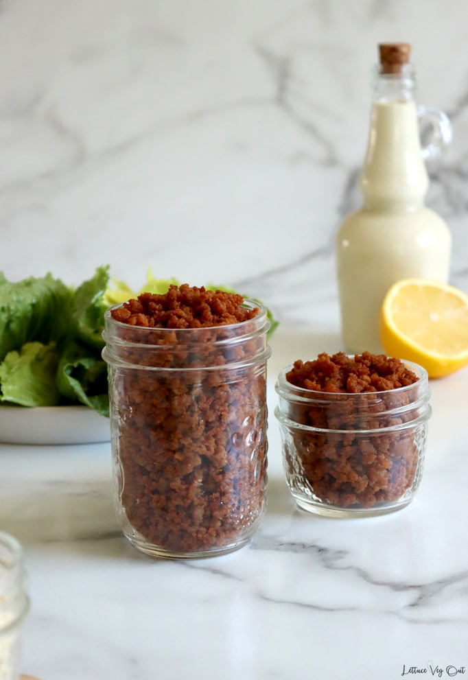 A medium and small mason jar filled with bacon bits on white-grey marble background. Plate of lettuce to the back left and jar of Caesar salad dressing with half a lemon to the back right.