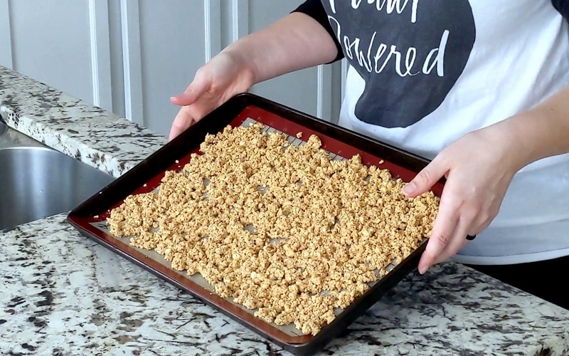 Hands hold up a baking tray topped with a silicone baking mat topped with a layer of crumbled, seasoning tofu bacon bits. They are raw and light brown in color.