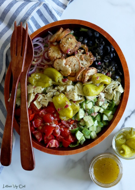 Top view of large oval dark wooden bowl filled with un-tossed salad (tomatoes, cucumber, pickled peppers, black olives, red onion, croutons and artichoke) with large wood fork and spoon resting on left edge of bowl. Blue-white striped towel along left edge with two small jars in bottom right corner.