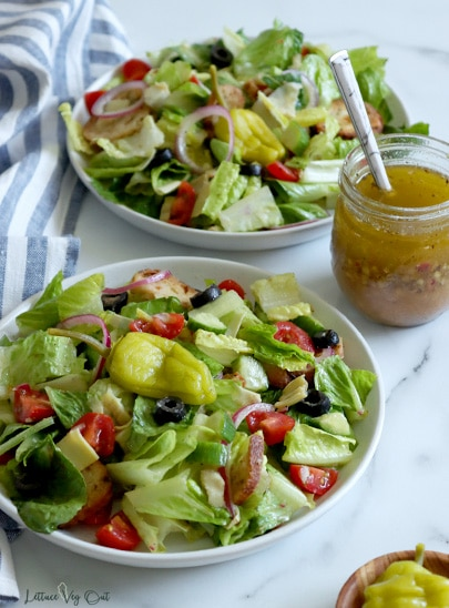 Two plates of tossed salad made with lettuce, tomato, black olives, cucumber, red onion, artichoke and croutons, garnished with pickled peppers. Small jar of Italian dressing with spoon in it to the right edge of image, between the two plates. White-blue striped towel along left edge. White-grey marble background.