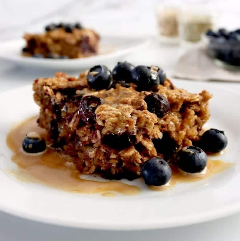 A served piece of vegan baked oatmeal served with blueberries and peanut butter drizzle. In the background is another piece of oatmeal and a small glass dish full of extra blueberries