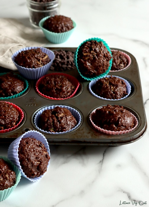 Muffin tin filled with chocolate muffins in colorful silicone muffin wrappers sitting on white-grey marble. A light brown towel placed over the muffin tray to the left, covering half the tray. Muffins removed from tray placed around the tray to the front, on top of the tray and in the back.