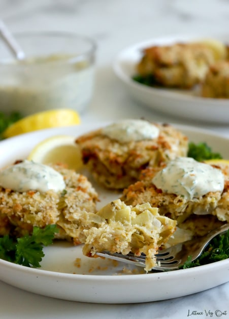 Forkful of breaded artichoke crab cake on white plate with three crab cakes each with a dollop of creamy sauce, and parsley plus lemon wedge garnishes. A second, blurred, plate of crab cakes to the back right and glass jar of creamy sauce blurred in back left. Grey marble background.