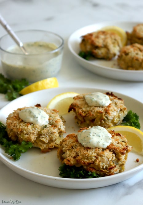 Three whole breaded artichoke crab cakes on a white plate, each topped with a scoop of white creamy sauce and garnished with parsley and lemon wedges. Second plate with crab cakes half cropped out and blurred to back right and small glass dish of creamy sauce with spoon in it blurred to back left.