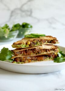 Stack of three quesadilla triangles stacked on a white plate, garnished with fresh jalapeno slices and cilantro. Two small glass bowls of cilantro, lime wedges and jalapeno slices blurred in back left. White-grey marble background.