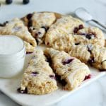 Square cropped image of an arrangement of triangle-shaped blueberry scones on a half wood half marble board with a small jar of white icing to the right. A spoon of icing sits to the back right.