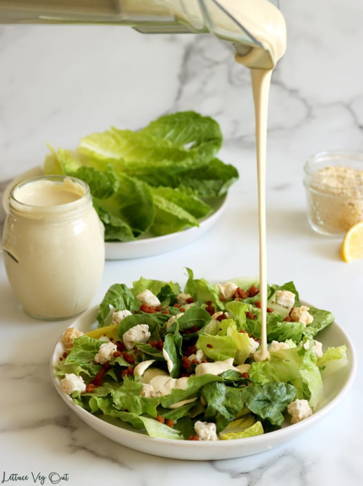 Image of a plate of chopped Romaine lettuce topped with bacon bits and small croutons with Caesar dressing being poured from a blender onto the salad. A jar of Caesar dressing and a plate of whole Romaine lettuce leaves sit to the back left and a small jar of vegan Parmesan and a lemon wedge sit to the back right.