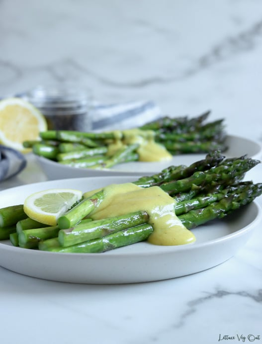 Side view of two round white plates each with a pile of cooked asparagus down the center, topped with light yellow, creamy sauce in the center of the asparagus spears with a lemon slice on top. White-grey marble background with a half lemon and jar of peppercorns to the back left of image.