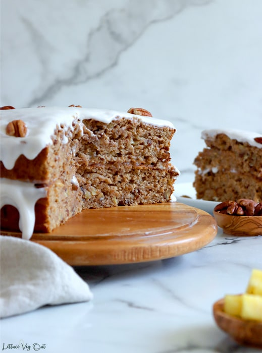 Double layer pineapple banana cake, with frosting on top and between layers, with a large piece cut out of it, sitting on a round wood cake board. A slice of cake, standing upright, sits behind the cake to the right and a small dish of chopped pineapple in the front right corner.