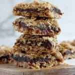 Stack of four date and oat crumble slices on a wood board with white-grey marble background. Wood board has other date slices blurred behind the stack.