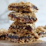 Square cropped image of a close up stack of four date and oat crumble slices on a wood board with white-grey marble background. Wood board has other date slices blurred behind the stack.