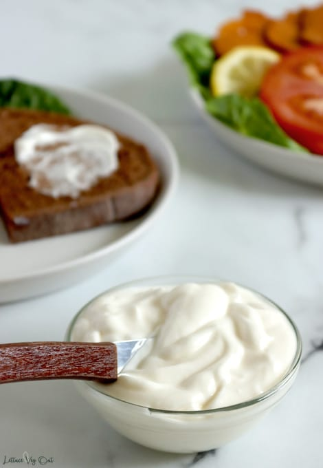 Small glass dish filled with mayonnaise with a dark wood handle butter knife resting in it. White plate with pumpernickel bread with smear of mayo sits to the back left and a plate of tomato, lettuce and vegan ham with a lemon wedge is cropped out in top right corner.