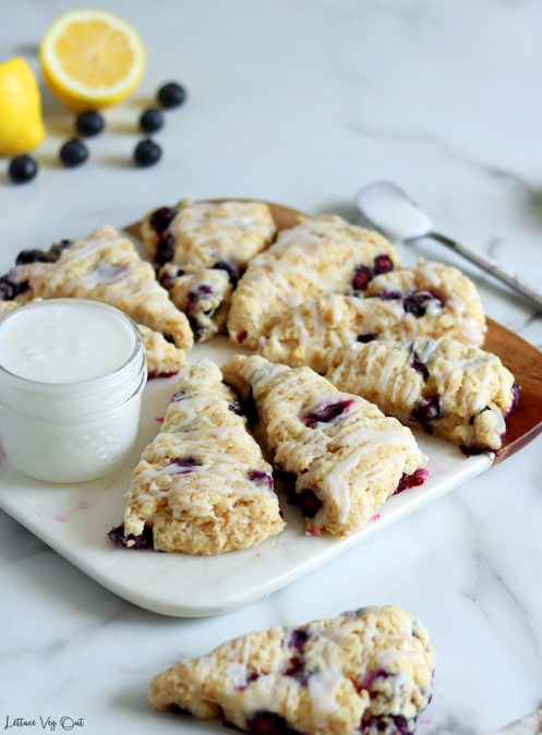 Arrangement of triangle-shaped blueberry scones on a half wood half marble board with a small jar of white icing to the right. A scone sits in front of the board with a spoon of icing to the back right and a lemon cut in half with blueberries sprinkled in top left corner.