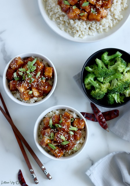 Top view of two small white bowls filled with General tao tofu (tofu cubes coated in brown-red sauce) garnished with green onion and white sesame seeds. A black bowl of broccoli sits to the center-right and a half-cropped out plate of rice topped with more tofu in top right. Decorated with chopsticks in bottom left and a few dry chili peppers.
