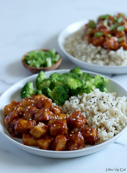 Plate of General Tso tofu garnished with white sesame seeds fills a third of the plate with a third filled with cooked rice topped with black sesame seeds and the other third with cooked broccoli. Second plate of tofu over rice blurred in back right with a small wood dish of chopped green onion between the plates to the left.