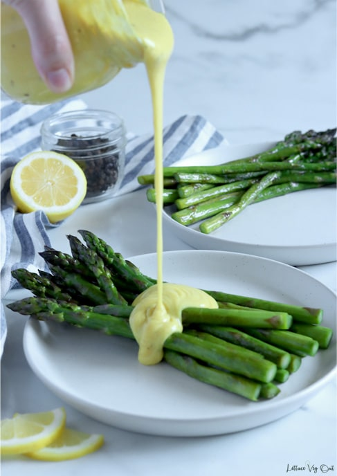 Glass jar of hollandaise sauce being poured over a pile of asparagus spears on a plate. A second plate of asparagus, without any sauce, sit in the back. Lemon slices to the front left of image with a white and blue stripped towel along the left side with a half lemon and jar of peppercorns to the back left.
