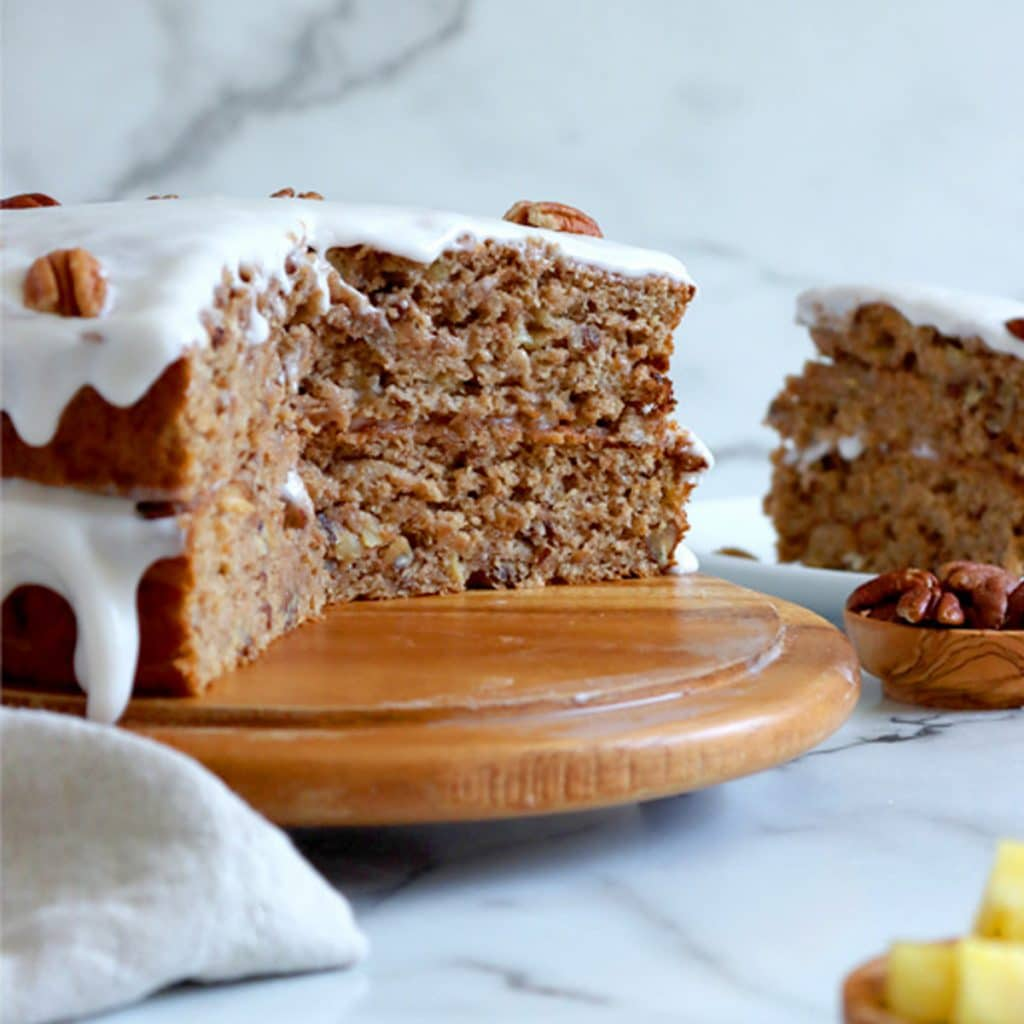 Square cropped image of double layer pineapple banana cake, with frosting on top and between layers, with a large piece cut out of it, sitting on a round wood cake board. A slice of cake, standing upright, sits behind the cake to the right and a small dish of chopped pineapple in the front right corner.
