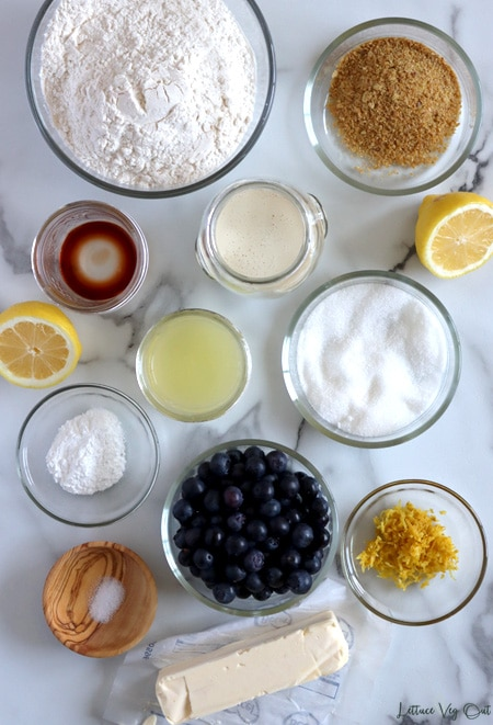 Arrangement of ingredients for blueberry scones in small glass jars or bowls sitting on white-grey marble. From top left (working right and then down): flour, ground flaxseed, vanilla extract, soy milk, lemon juice, sugar, baking powder, blueberries, lemon zest, salt, stick of vegan butter; with two lemon halves for decoration on each edge.