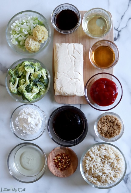 Arrangement of ingredients in small glass bowls or jars on white-grey marble counter with a small wood board in top right corner. From top left: chopped green onion with grated ginger, soy sauce, rice vinegar, raw broccoli florets, block of tofu, sesame oil, ketchup, corn starch, hoisin sauce, brown sugar, water, chili flakes, cooked rice.