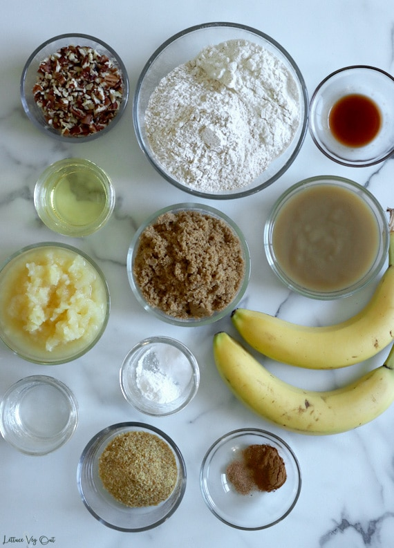 Top view of an arrangement of ingredients in small glass bowls sitting on white-grey marble. From top left corner: chopped pecans, flour, vanilla extract, oil, brown sugar, applesauce, crushed pineapple, baking powder and soda, two unpeeled bananas, water, ground flaxseed, spices.