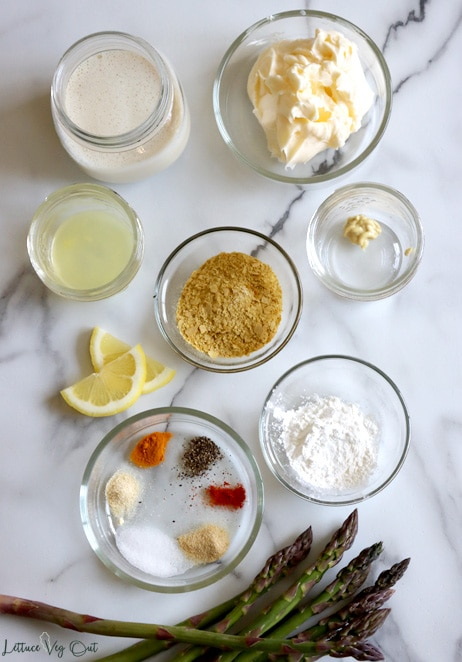 Top view of an arrangement of ingredients in small glass bowls and jars on white-grey marble background. From top left: soy milk, vegan butter, lemon juice, Dijon mustard, nutritional yeast, lemon slices (decoration), corn starch, spice mix, fresh asparagus spears (decoration).