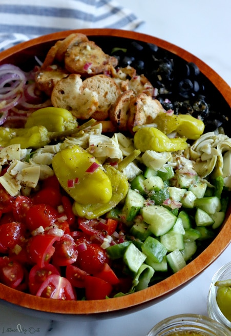 Large oval dark wood bowl filled with un-tossed Italian salad (tomato, cucumber, artichoke, black olives, croutons, red onion, pepperoncini peppers). White and grey marble background with white and blue stripped towel in top left corner.
