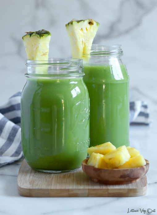 Two jars filled with bright green juice and garnished with triangle of pineapple sitting on light wood board over white-grey marble background. Small wood dish of pineapple pieces on the wood board to the front right corner. Blue-white stripped towel wraps around the left side of the wood board.