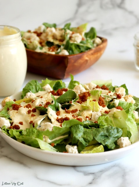 Straight on view of a plate of chopped Romaine lettuce topped with bacon bits and small croutons covered with a drizzle of Caesar dressing.