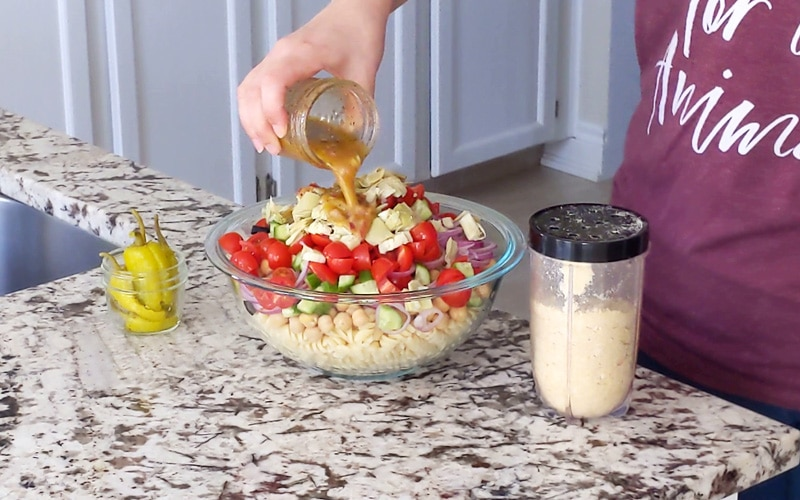 Hand pouring orange salad dressing onto prepped pasta salad and chopped vegetables in a large glass bowl. A plastic shaker jar of vegan Parmesan sits to the right with a small jar of pickled peppers to the left.