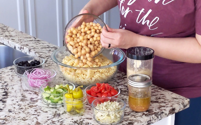 Hands pour chickpeas over cooked rotini pasta in a large glass bowl. Small glass bowls of chopped vegetables sit on granite counter around the large bowl (black olives, sliced red onion, cucumber, pickled peppers, chopped tomato, artichoke, jar of salad dressing and shaker of parmesan).