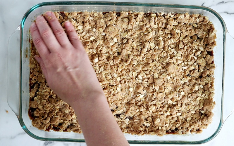 A hand is pressing oat crumble on the top left corner of a large glass baking dish. The dish is covered with this crumble mixture.