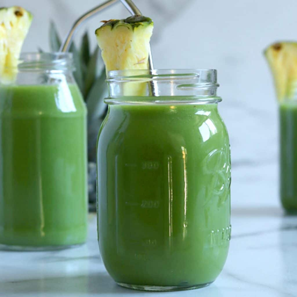 Square image of a straight on shot of a mason jar filled with spinach pineapple smoothie, garnished with pineapple and with a bent metal straw in the jar. Two other jars sit blurred in the back along with the top of a pineapple that is hidden behind the jar on the left.