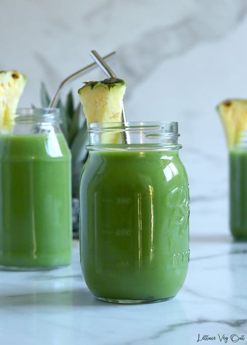 Straight on shot of a mason jar filled with spinach pineapple smoothie, garnished with pineapple and with a bent metal straw in the jar. Two other jars sit blurred in the back along with the top of a pineapple that is hidden behind the jar on the left.