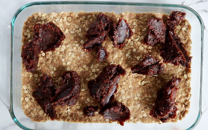 Top view of a large glass baking dish filled with a firm layer of oat crumble crust at the bottom and topped with piles of pureed dates across the top.