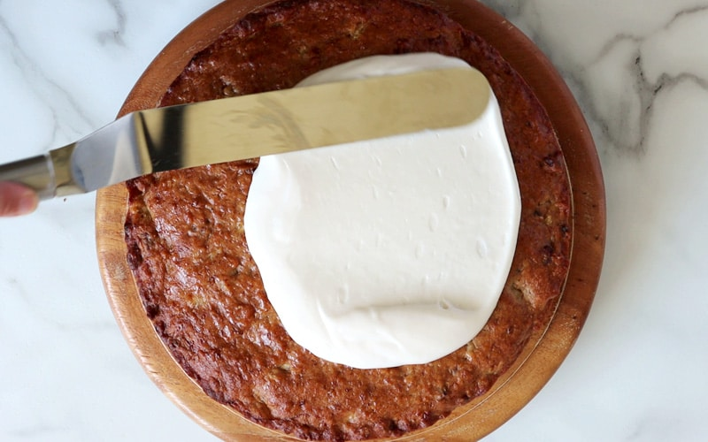 Thick white frosting being spread with a metal spatula over top a dark brown, round cake.