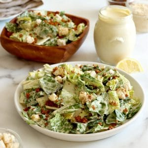 Square cropped image of a large white plate topped with tossed Caesar salad with bacon bits and small croutons with a square wood bowl of the same salad behind the plate. Jar of Caesar dressing sits to the right between the plate and bowl with two jars behind the dressing (bacon bits and Parmesan) with a folded light brown towel in back left corner and jar of croutons in bottom left corner.
