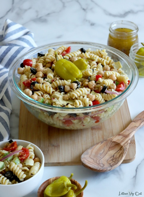 Large glass bowl of rotini pasta salad on wood board with large wood serving spoon. White-grey marble background with white and blue striped towel on the left side. Bottom left corner has small white bowl of pasta salad and wood dish of peppers; top right corner has jar of salad dressing and pepperoncini peppers.